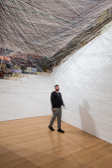 A visitor explores Jean Shin's work Unraveling, a canopy made from sweaters donated by Asian American art communities.